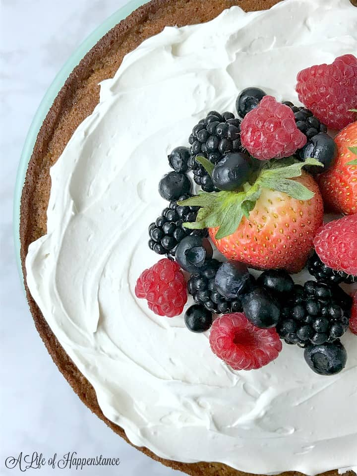 A vanilla almond flour cake topped with honey Italian meringue and fresh berries.