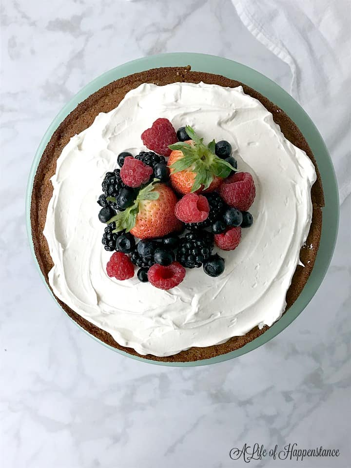 An overhead photo of the vanilla almond flour cake topped with honey Italian meringue and fresh berries.