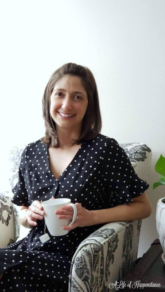 Jennifer from A Life of Happenstance sitting in an arm chair holding a white cup of tea.