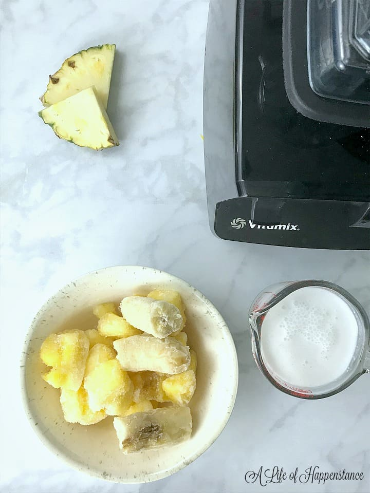 A bowl filled with frozen bananas and pineapple chunks next to a measuring cup of coconut milk.