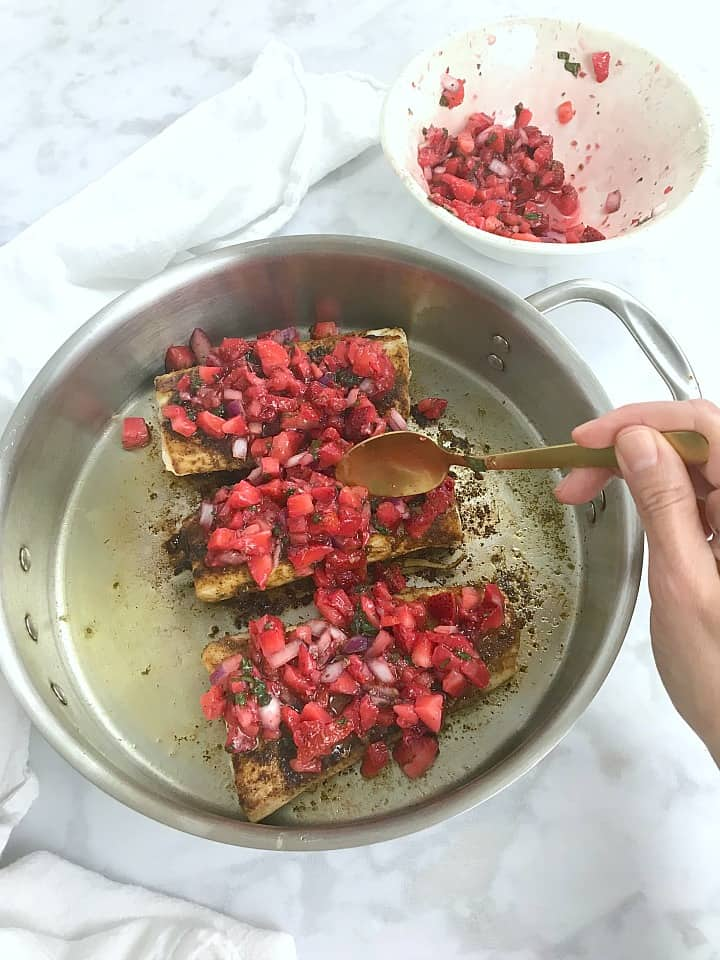 Spooning the strawberry salsa on top of the cooked mahi mahi.