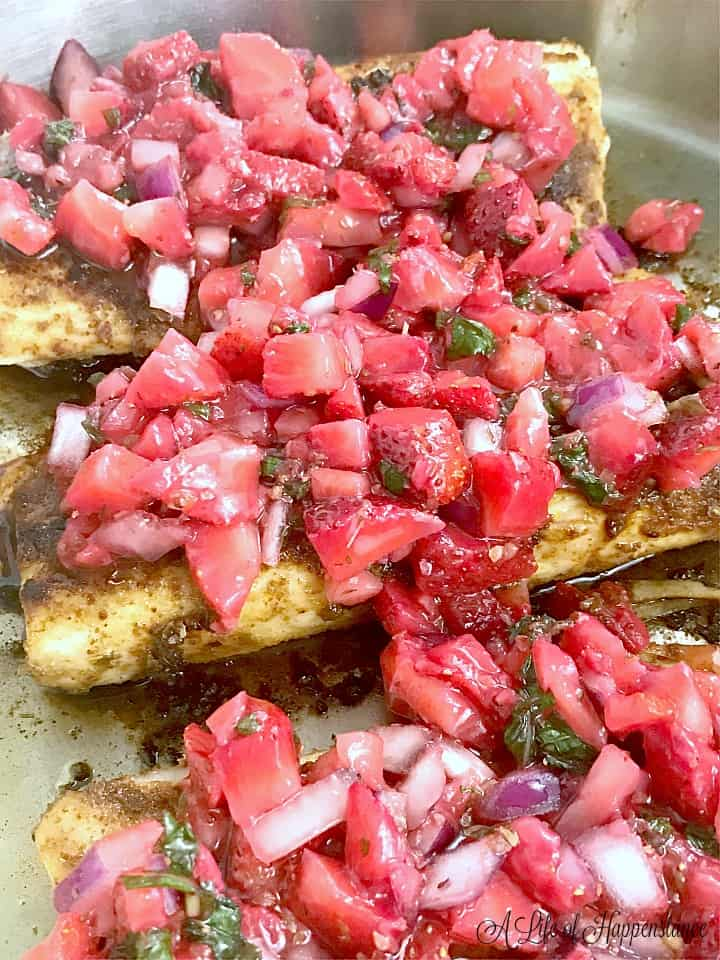 A close up photo of the seared mahi mahi with strawberry salsa in the frying pan.