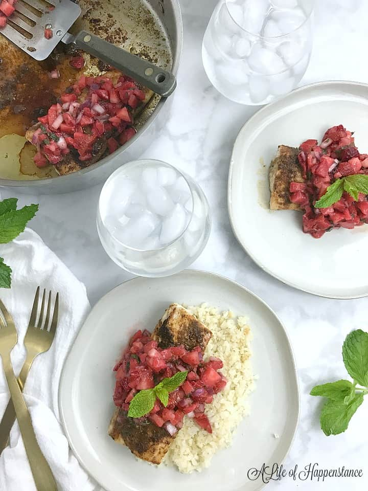 Two with plates with the seared mahi mahi and strawberry salsa on them. Glasses of sparkling water and a frying pan with another fish filet are also on the table.