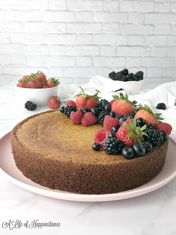 A side view of the almond flour cake on a pink plate decorated with fresh berries. The background of the photo has two white bowls filled with fresh strawberries and blackberries.