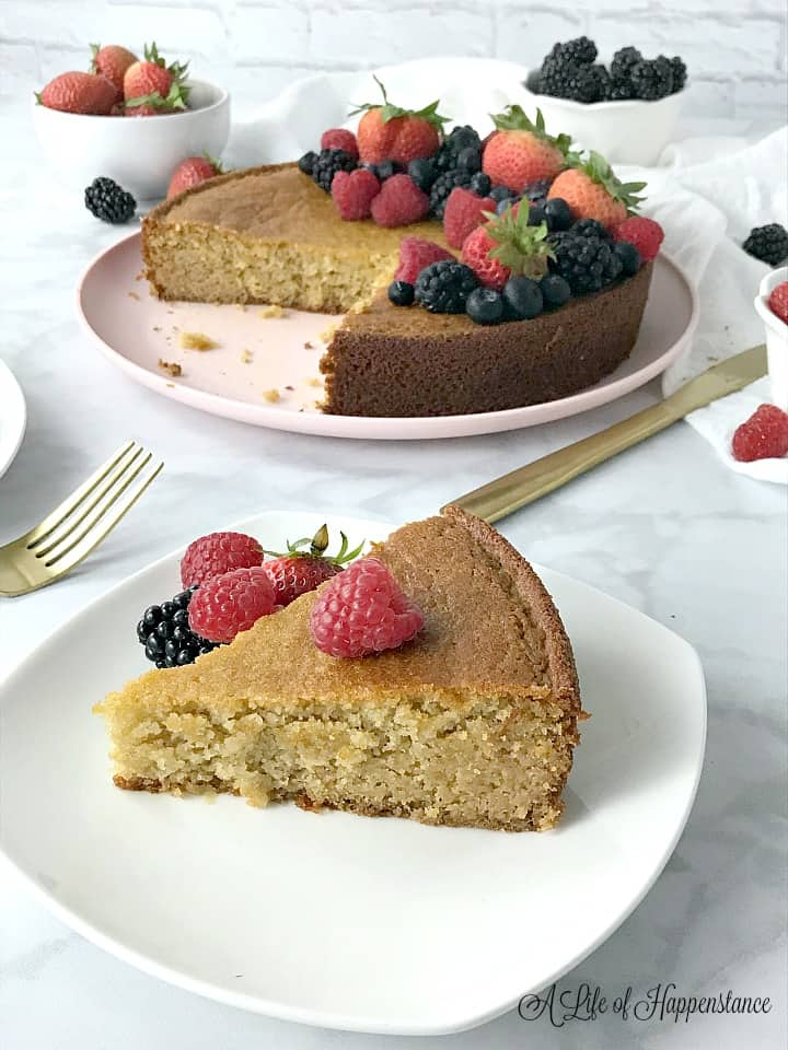 A slice of cake on a white plate with fresh berries. The rest of the vanilla cake is in the background.