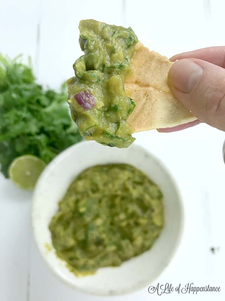 A cumin lime tortilla chip with broccoli dip (broccomole) on it.