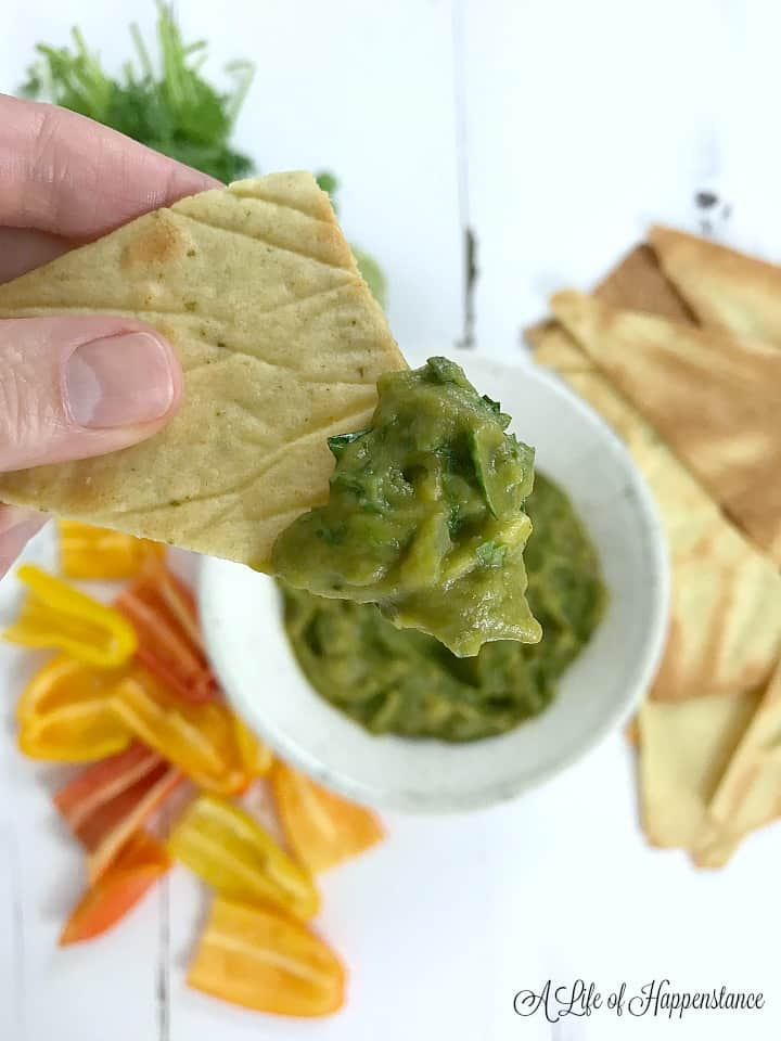 A hand holding a chip that's been dipped in the broccoli dip (broccomole).