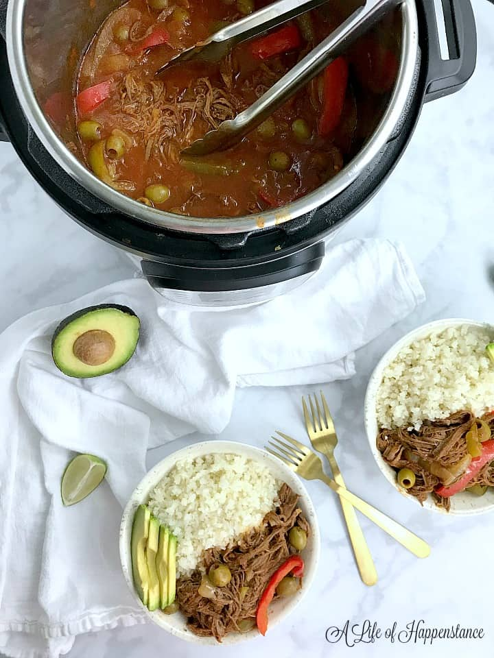 Two bowls filled with ropa vieja, cauliflower rice, and avocado with the rest of the beef in the Instant Pot.