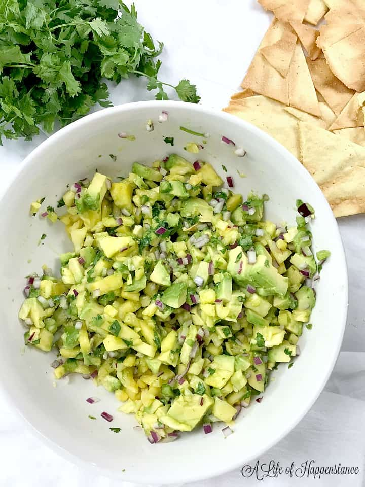 A large white bowl filled with pineapple avocado salsa. The bowl is surrounded by fresh cilantro and cumin lime tortilla chips.