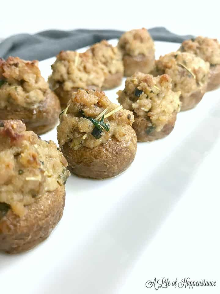 Baked sausage stuffed mushrooms in two rows on a white plate.