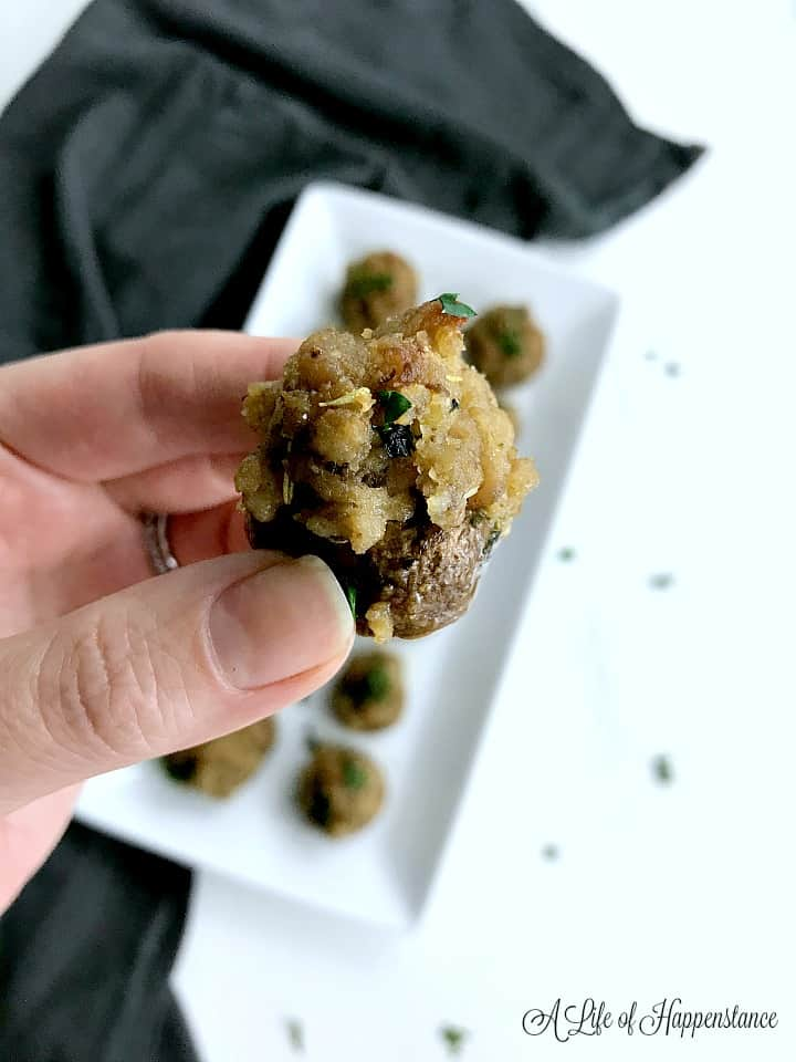 holding up a stuffed mushroom with the rest in the background on a white plate.