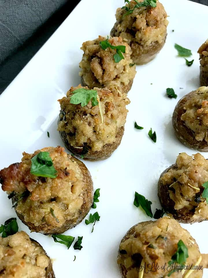 Sausage stuffed mushroom caps garnished with chopped parsley on a white plate.