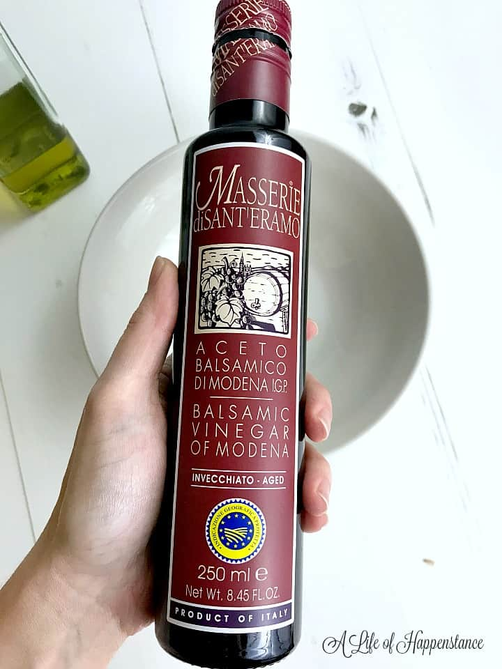 Holding a bottle of Msserie si Sant'Eramo balsamic vinegar over a white bowl.