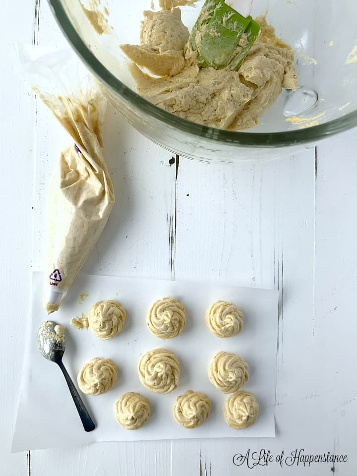 Overhead photo of buttercream rosettes on parchment paper next to a piping bag and more buttercream in a glass mixing bowl.