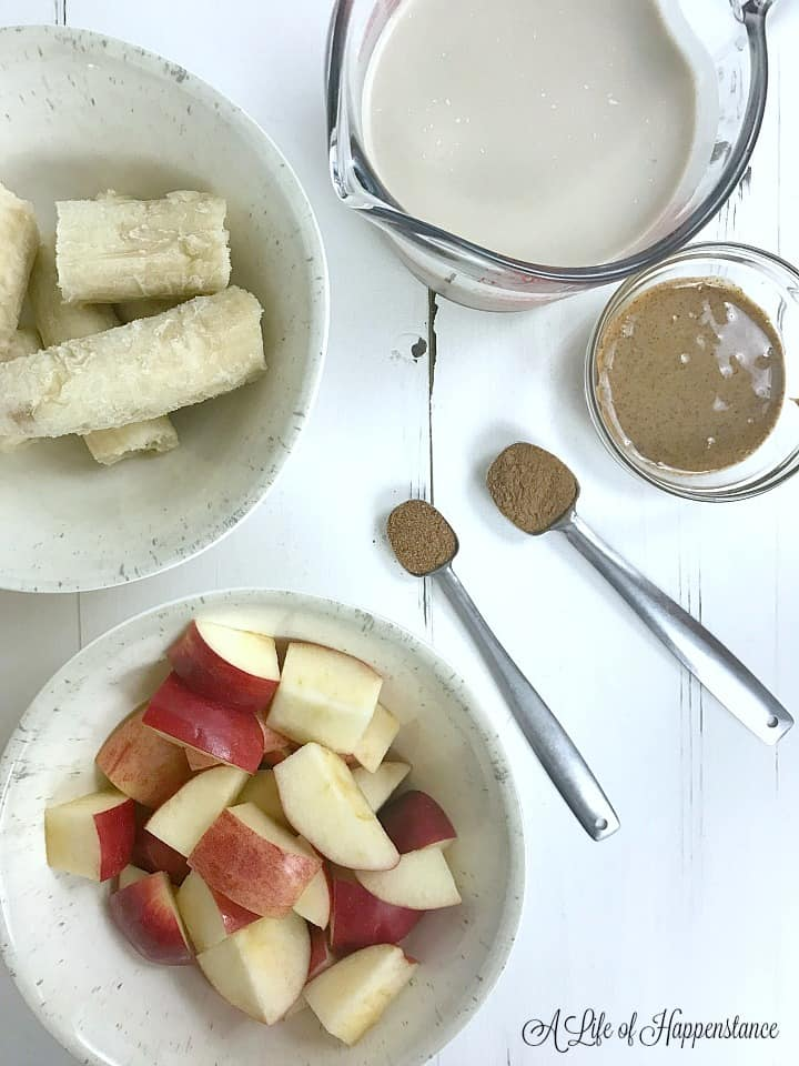 All ingredients needed for the smoothie. Frozen bananas, walnut milk, almond butter, nutmeg, cinnamon, and apples.