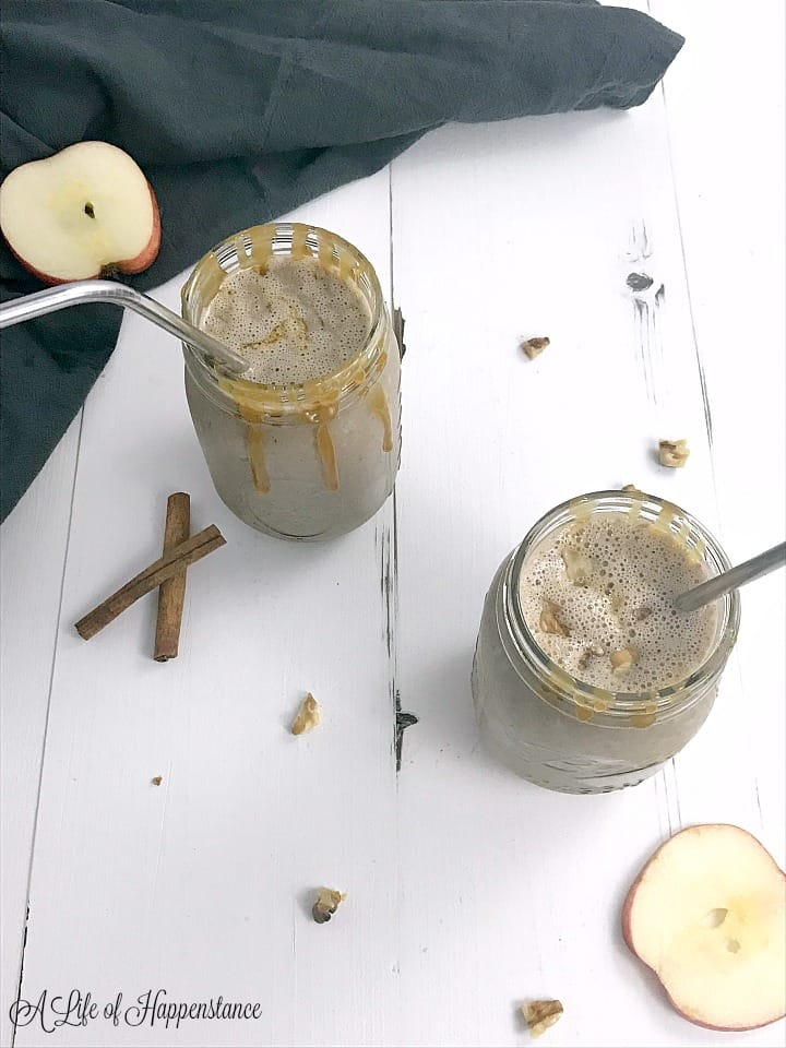 Two mason jars filled with the apple cinnamon smoothie and garnished with a caramel drizzle.