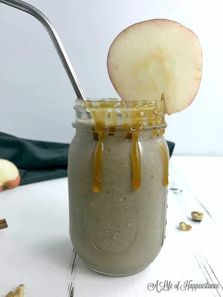 Apple cinnamon smoothie in a mason jar garnished with an apple slice, a caramel drizzle, and a metal straw.