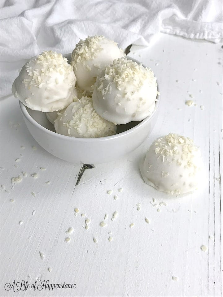Coconut truffles in a white bowl sitting on a white table.