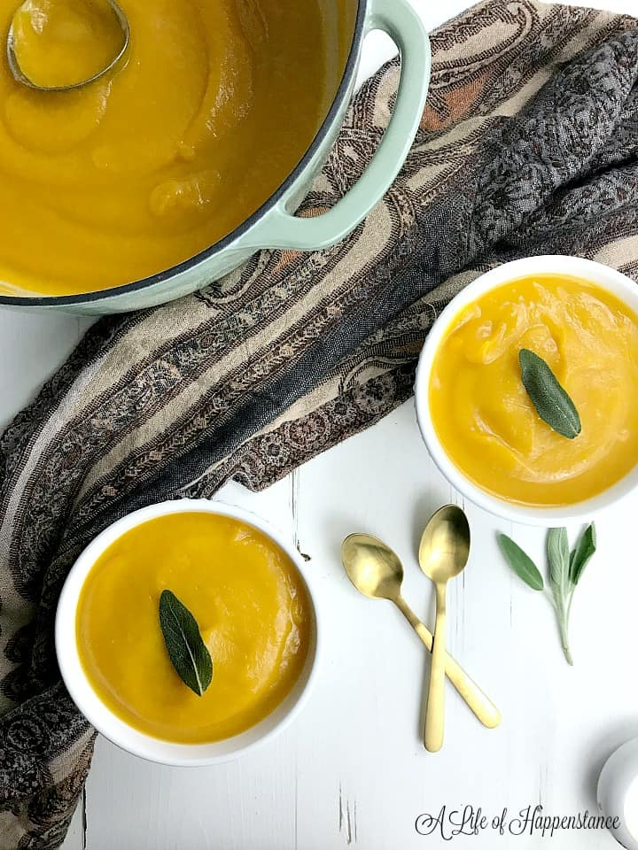 A pot of paleo butternut squash soup along with two bowls filled with the soup and garnished with fried sage leaves.