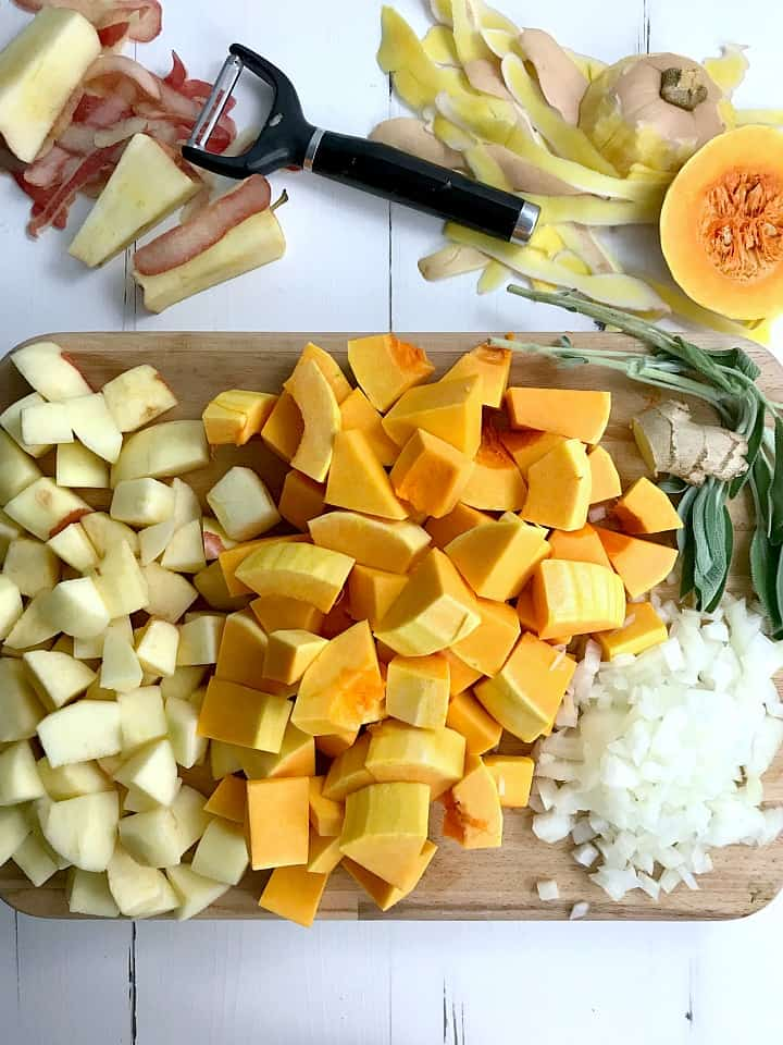 A cutting board filled with chopped apples, chopped butternut squash, chopped onions, ginger root, and sprigs of sage.