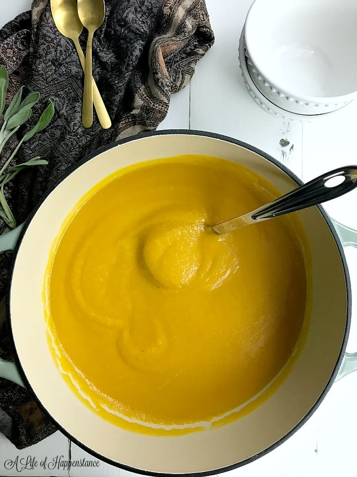 Large pot of the easy butternut squash apple soup recipe on a white table surrounded with white bowls, a brown kitchen towel, and fresh sprigs of sage.