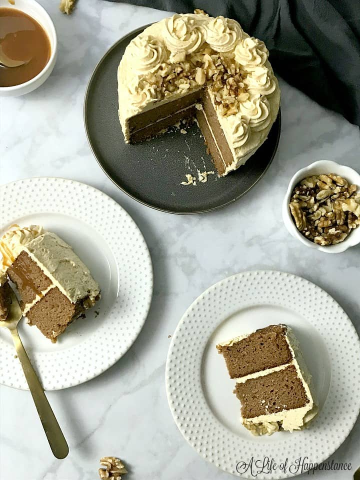 Slices of cake on white plates with the rest of the cake in the background.