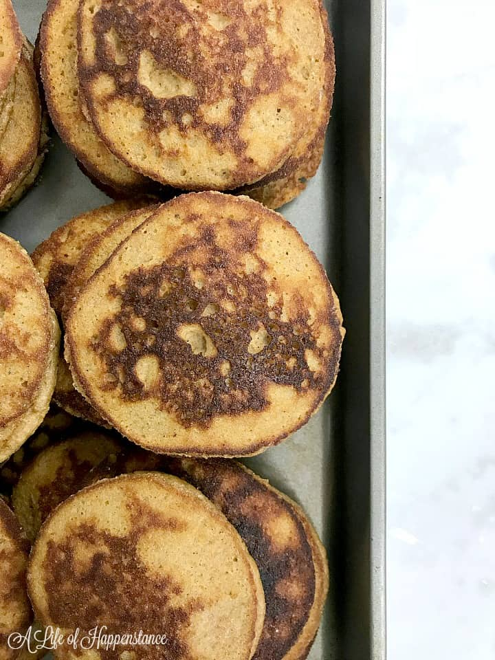 A close up of the paleo pumpkin pancakes on a baking sheet.