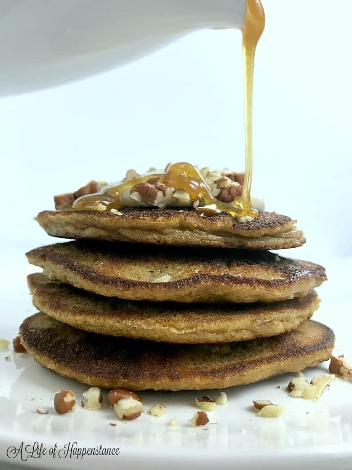Pouring honey cinnamon syrup on a stack of gluten free pumpkin pancakes.