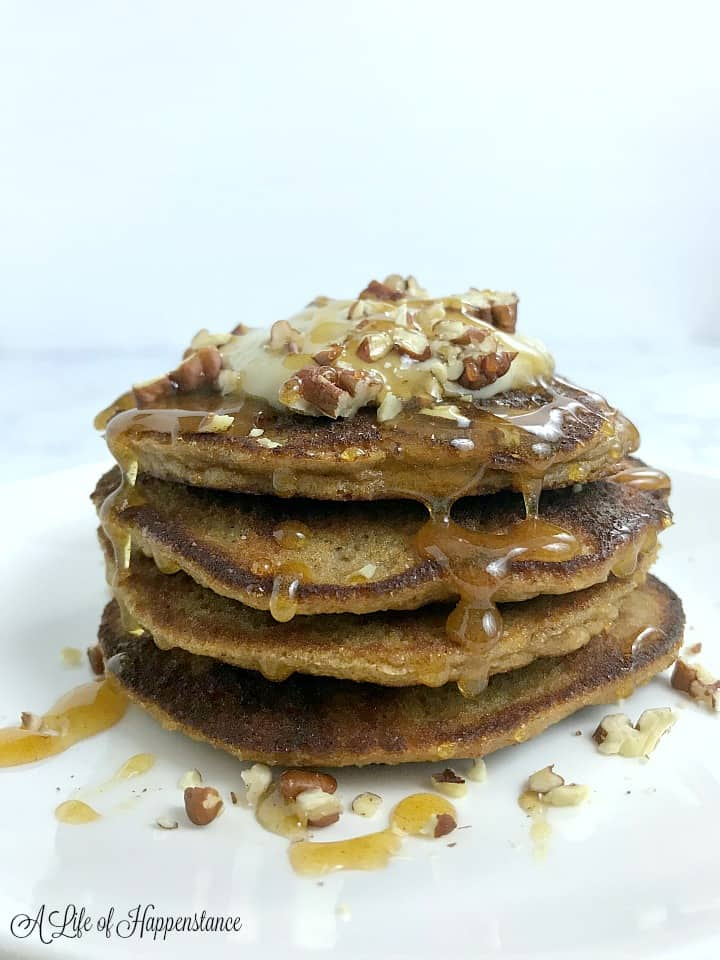 A stack of four paleo pumpkin pancakes topped with cashew cream, chopped walnuts, and honey cinnamon syrup.