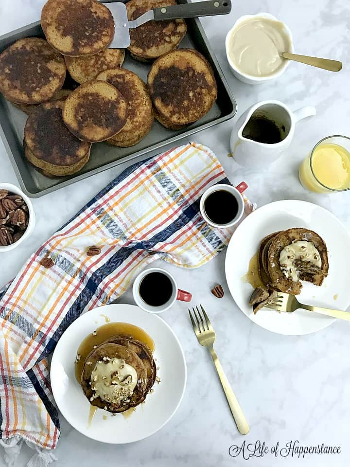 A table set with a sheetpan filled with gluten free pumpkin pancakes, espresso filled coffee cups, a bowl of cashew cream, and two plates with stacks of pancakes and syrup.