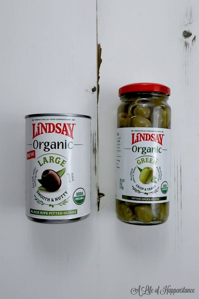 One can of large black pitted olives and one bottle of green pitted olives on a white table.