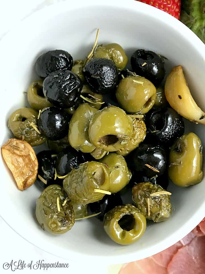 Close up photo of roasted olives and garlic covered in olive oil, thyme, and rosemary.