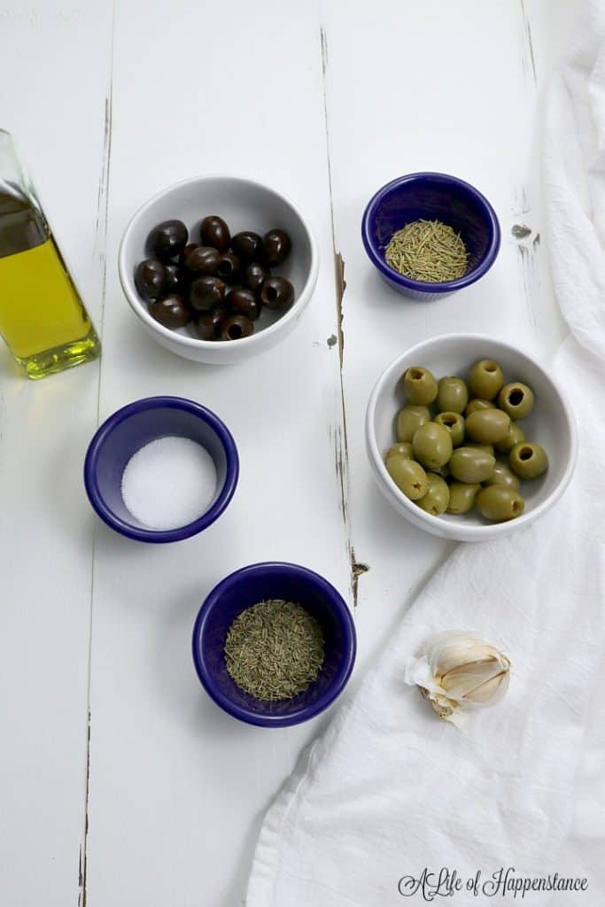 All the ingredients for the roasted olives in bowls on a white table.