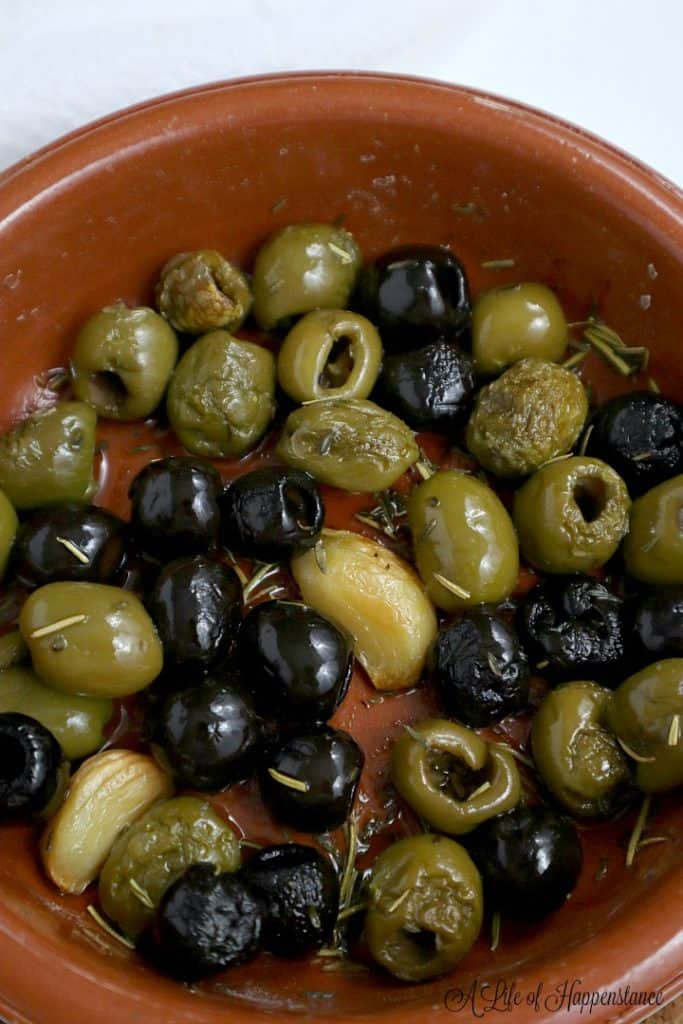 Roasted olives in an oven safe brown baking dish.