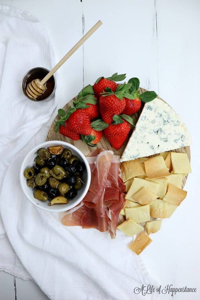 A small charcuterie board filled with almond flour crackers, strawberries, prosciutto, olives, and a wedge of cheese.