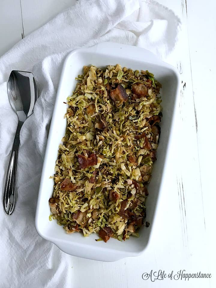 An overhead shot of the shaved brussel sprouts with bacon in a white baking dish on a white table.