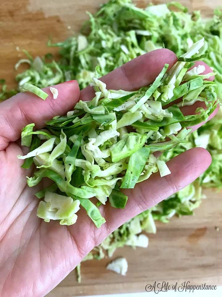 Holding a handful of the shaved brussel sprouts.