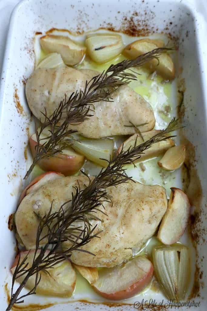 Up close photo of two baked apple cider chicken breasts in a white baking dish surrounded by shallots, apples, garlic, and rosemary sprigs.