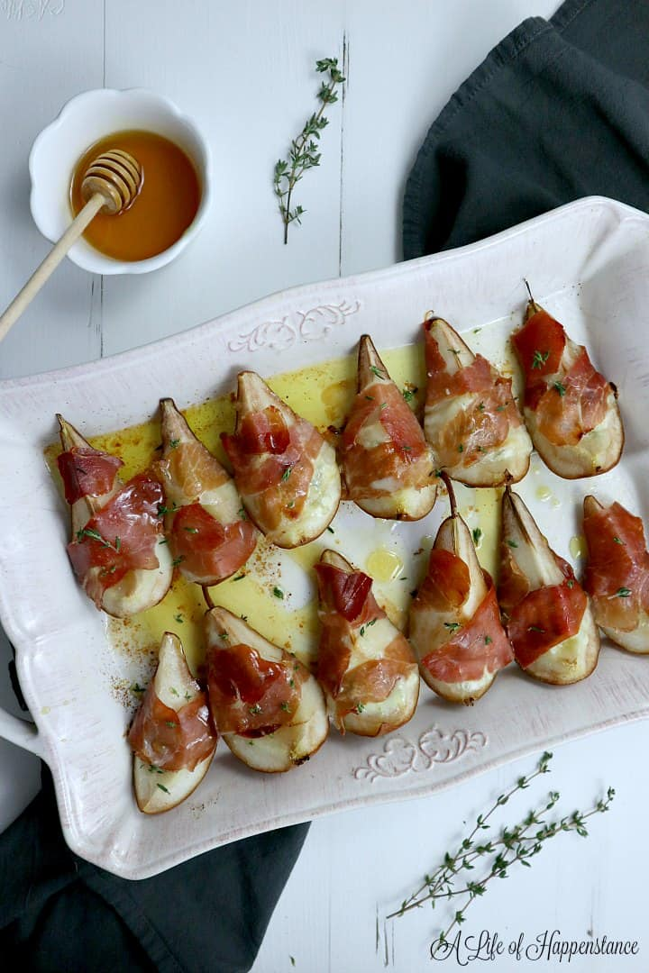 Twelve prosciutto wrapped pears in a cream colored baking dish on a white table and black grey napkin.