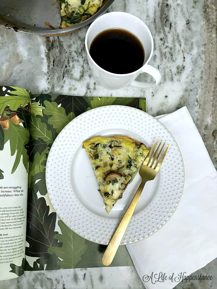 A frittata slice on a white plate next to a gold fork.