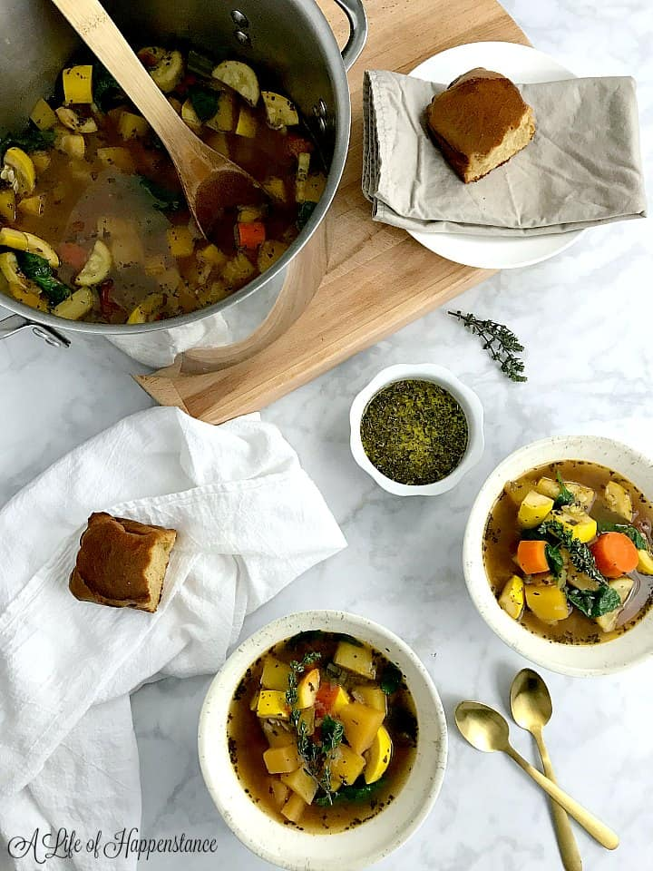 An overhead photo of two bowls filled with the healthy vegetable soup on a marble table. The rest of the soup is in a large pot on a wooden cutting board.