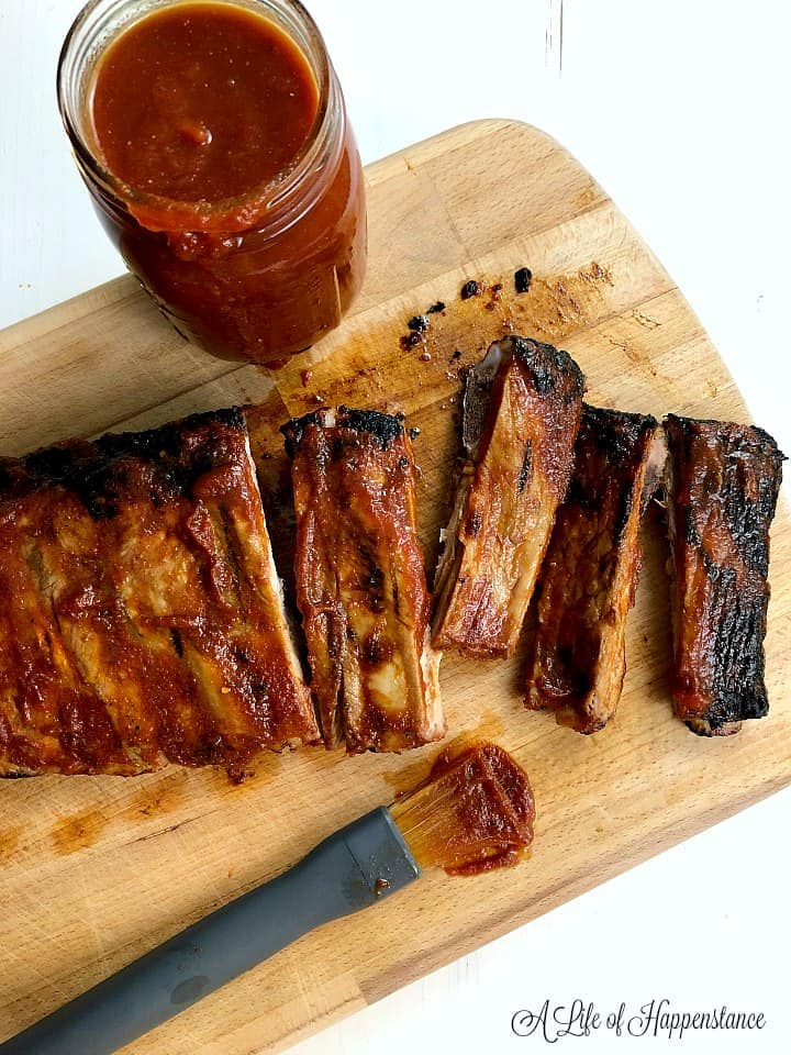 A wood cutting board with grilled ribs, a mason jar filled with honey bbq sauce, and a brush with sauce.