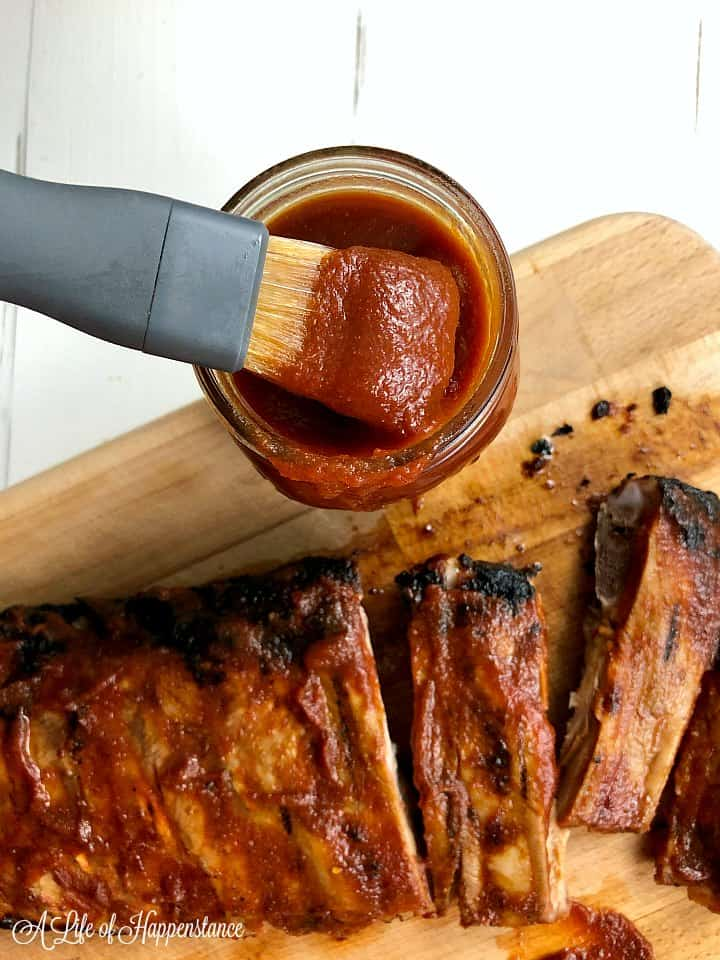 Ribs on a wood cutting board and a brush filled with the bbq sauce.