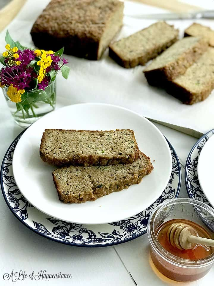 Two slices of Paleo zucchini bread on a white plate with the rest of the loaf in the background.