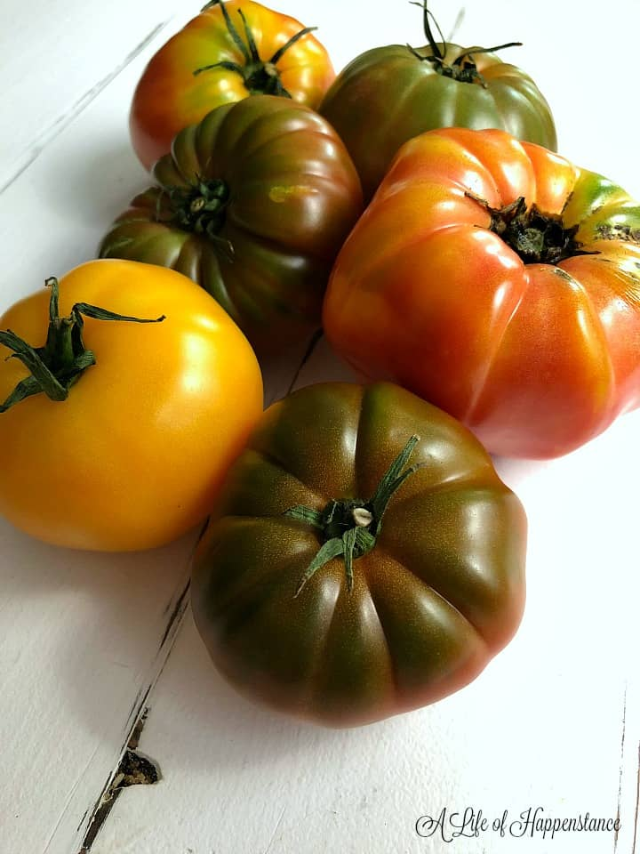 Six heirloom tomatoes on a white table.