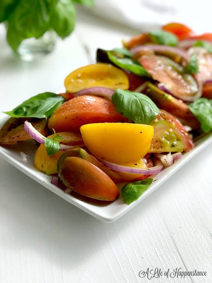 A close up photo of the heirloom tomato salad on a white plate with fresh basil in the background.