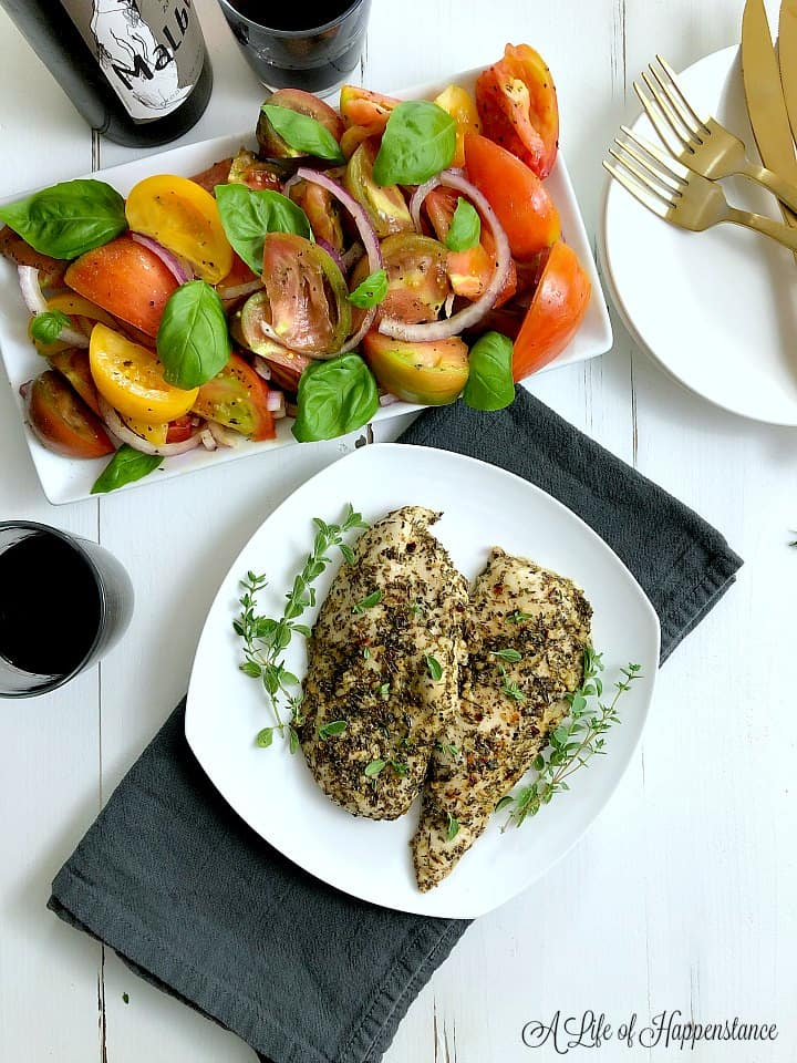 Oregano lemon chicken on a white table along with red wine and an heirloom tomato salad.