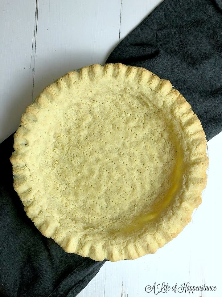 A baked almond flour pie crust cooling on a gray kitchen towel.