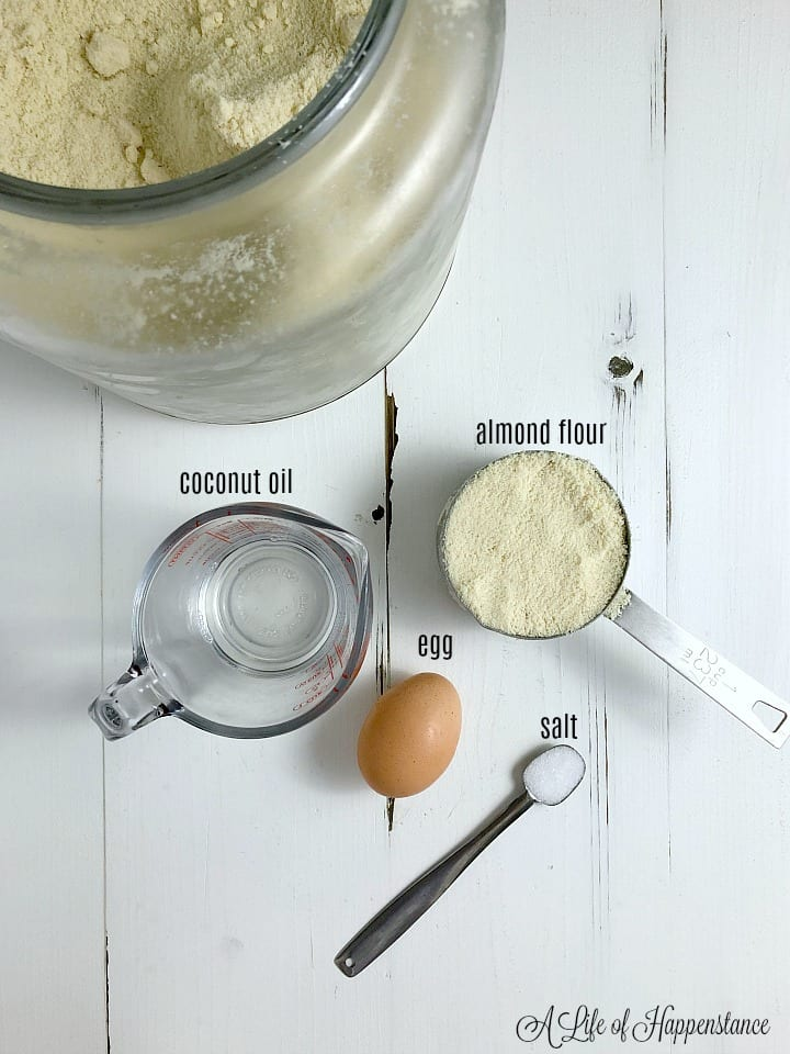 The ingredients for the pie crust on a white table; coconut oil, egg, salt, and almond flour.