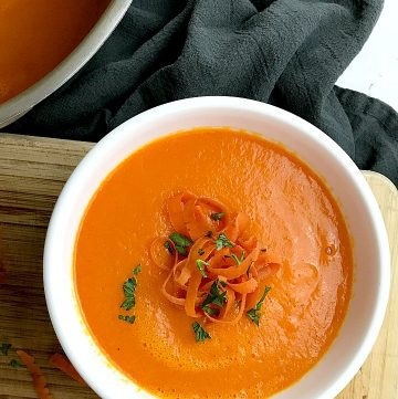 A white bowl filled with the ginger carrot soup recipe.